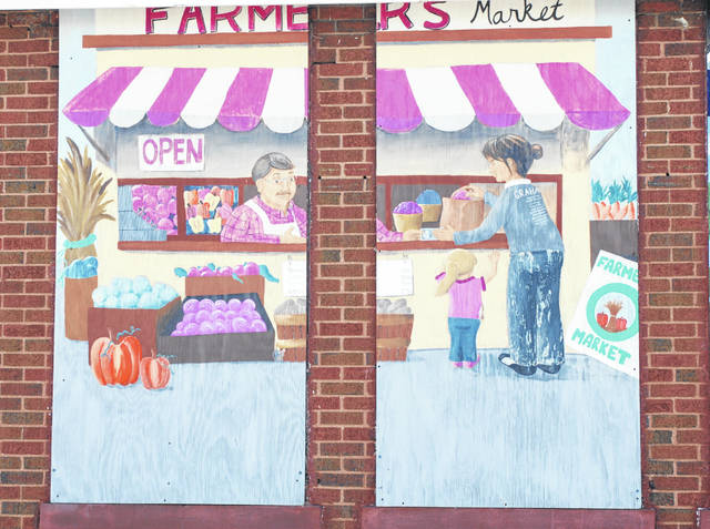Pictured is a mural depicting the Champaign County Farmers Market at the corner of East Market and Locust streets in Urbana.