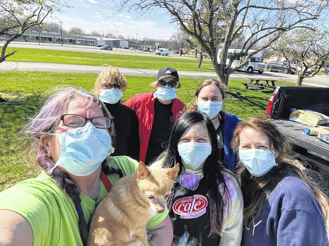 This group from Only Believe Ministries Urbana painted the exterior of windows to cheer nursing home residents during the pandemic: Tiger Franks and Peanut - left, Lilah Risner - left back, Samara Risner - center back, Kayla Gabriel - back right, Lindsey Kirker - front right, and Hagen Dyer - middle front.
