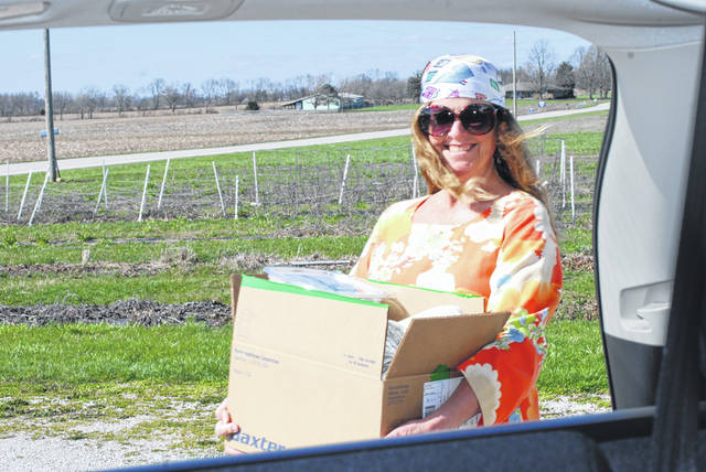 Pam Bowshier of Hippie and The Farmer coordinates the weekly virtual farmers' market. Items purchased through the market can now be picked up at a new location, Oakview Farms on state Route 54. Previously, pickup was at the Champaign Family YMCA. In photo, Bowshier carries an order to a waiting vehicle on Thursday.