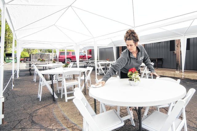 Jenni Eby of The Farmer's Daughter in Urbana cleans a table on Thursday in preparation of the return of outdoor dining today after the Covid-19 stay-at-home order. The restaurant erected tents to accommodate diners who wish to eat on-site outdoors starting today. Indoor dining is scheduled to reopen May 21 under strict guidelines.