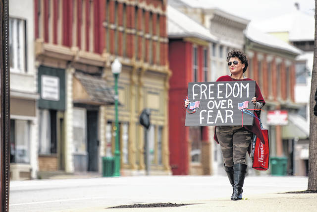 Urbana businesswoman Laura Alban walks with a sign to protest the COVID-19 Stay-at-Home order on Saturday afternoon on South Main Street in Urbana. Alban organized the local protest that was scheduled be a peaceful statewide demonstration in local communities on Saturday. Alban owns an essential oils business in Urbana. Approximately 10 people participated in the protest.