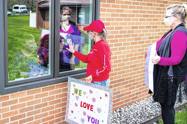 Rhonda Adams greets McAuley Center resident Phyllis Rittenhouse (at left, behind the window) during a Women of the Moose outreach visit recently.