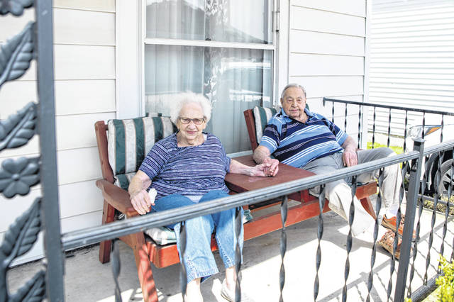 "The Evanses of St. Paris pose for a local photography project called ""Porchtraits"" by John Coffman — who is depicting local families who are making the most of Ohio's stay-at-home orders to fight the spread of the COVID-19 pandemic. Pictured in the theme ""70 years of marriage"" are Charles & Libby Evans marking their 70th wedding anniversary with a drive-by parade celebration in their honor. They were married on May 6, 1950 and married in this house that they still live in. For more, contact Coffman directly on Facebook at his John Coffman Photography page, or text him at 937-206-0254."