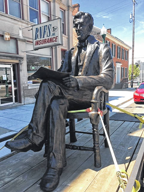 """A bronze sculpture of Abraham Lincoln sits on a trailer on Miami Street in downtown Urbana. The statue has been sitting in front Urbana artist Mike Major's studio for several days, waiting to be transported to its destination. The nonprofit American Veterans Heritage Center, in partnership with the Lincoln Society of Dayton, sought to raise $379,000 to establish a 100-foot by 100-foot park next to the library on the Dayton VA campus to honor Lincoln. The park will feature the bronze sculpture of Lincoln. Fifteen feet high, the statue is seated Lincoln, pen in one hand and the 1865 legislation creating """"national soldiers and sailors asylums"""" to care for disabled and wounded veterans in the other. It will be erected gazing toward the VA Medical Center structures."""