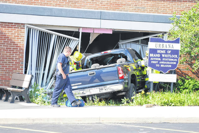Emergency responders work at the scene of a crash Wednesday at approximately 5:30 p.m. A truck went through the window of the Champaign County Library.
