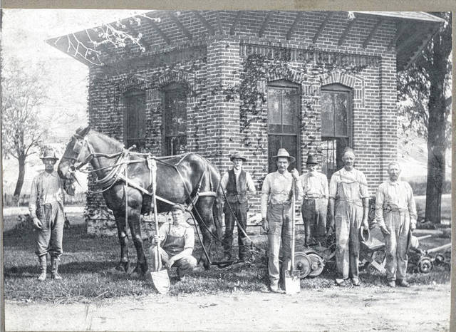 This circa 1915 photo, shared by the Champaign County Historical Museum, shows grave diggers and workers assembled before Oakdale Cemetery's hexagonal office building, which still stands. Note the tools used by the workers are shovels and a horse hitched to an unidentified device. Most things used currently at Oakdale for grave digging and grounds maintenance are gasoline- or diesel-powered machines. This illustrates the dramatic change from 100 years ago brought about by the availability and utilization of petroleum fuels.