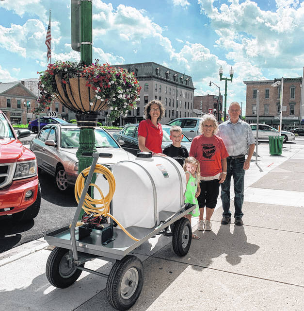 Weidmann Electrical Technology's donation of a watering system to the Monument Square District (MSD) is making it less time-consuming for MSD board President Vicki Deere-Bunnell and other MSD members to water flowers in the center of the roundabout and other areas of Monument Square. Mark Hunter and other Weidmann employees worked with MSD to create a more efficient watering system, and Weidmann then donated the system to MSD. In addition, the city of Urbana allowed MSD access to the water system on the Square and installed flower baskets on downtown poles. Shown in the photo are, from left, MSD members Kara Stephens (and her children), Deere-Bunnell and Hunter.