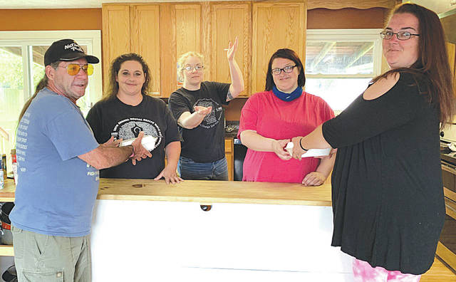 From left are Recovery Zone delivery driver Forest Saylor, Assistant Director Rose Trydle, Director Lisa Brandel, assistant chef Taylor Lloyd and delivery driver Heather Bailey. The photo was taken in the small kitchen at Recovery Zone, where meals to be delivered are made.
