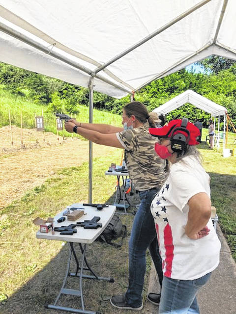 Women-on-Target instructor Cindy Scott observes while clinic attendee Tory Cordell takes a practice shot.
