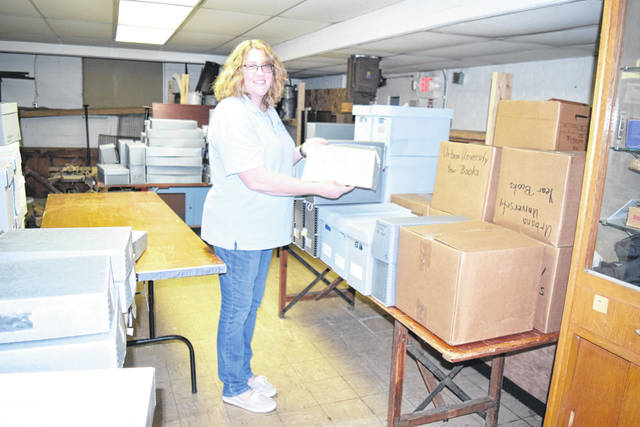 Cheryl Ogden, curator of the Champaign County Historical Museum, holds the deed providing land for Urbana University while standing amid dozens of boxes containing historic UU documents and artifacts.