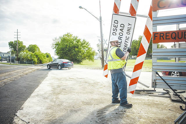 "Safety Services Solutions removes the last ""Road Closed"" sign from the railroad construction on N. Main Street at Boyce Street on Friday evening. The road is now officially open."