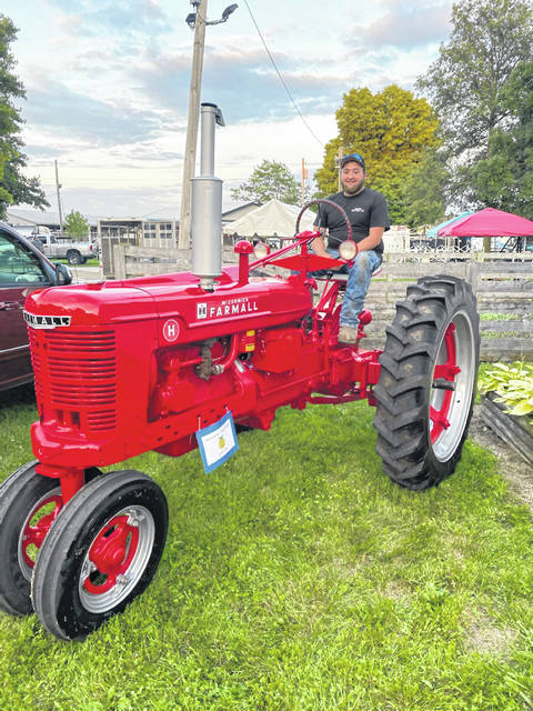 Justin Preece parks the Farmall H to be displayed at the Champaign County Fair.