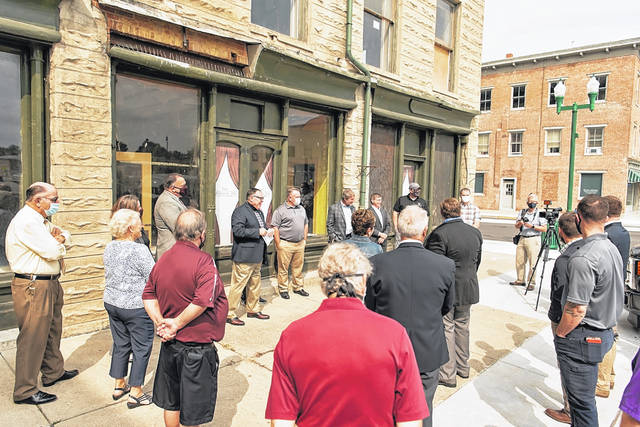 Community leaders and project managers gather in front of the Douglas Hotel on Thursday morning to announce the Legacy Place senior citizen housing project is moving forward.