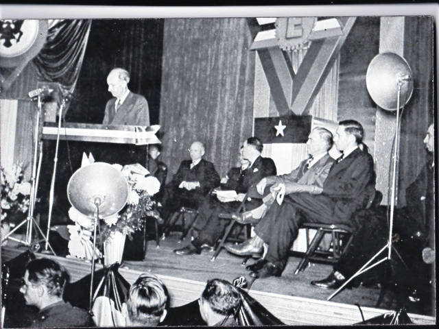"""Given that this year is the 75th anniversary of the end of WW II, the Champaign County Historical Society looks back at the county's involvement. The Army-Navy E Production Award was given during WW II to companies and their employees: """"For high achievement in the production of war material."""" It recognized the finest type of unity and cooperation between those on the fighting front and those on the production front. This photo (#3940) is of Warren G. Grimes accepting on behalf of the employees and management of Grimes Manufacturing Co. the Army-Navy E Award on Nov. 26, 1942, at the Gloria Theater. Grimes manufactured lights for all military aircraft."""