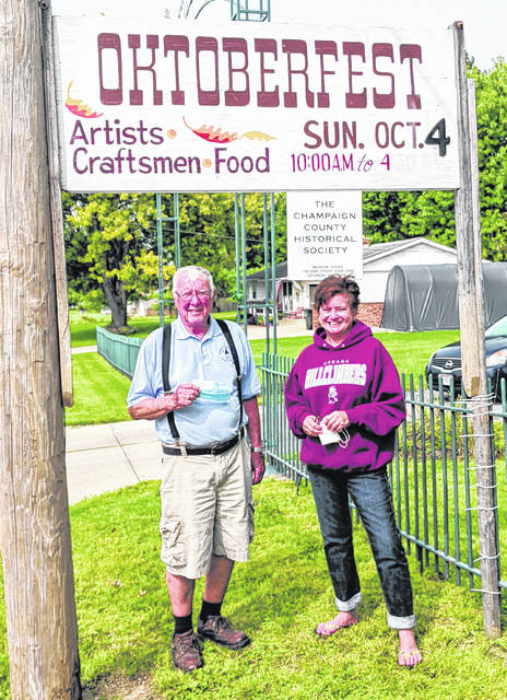 Dick Virts and Beth Adair stand under the sign that for many years has welcomed people to the Champaign County Historical Society's Oktoberfest, held each year since 1972 at the society's museum at 809 East Lawn Ave.