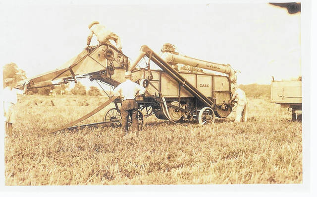 Then – This is a circa 1930 photo (#2501) of a threshing machine manufactured by Case in use on the Kiser/Furrow farm located just north of St. Paris.