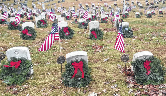 Participants of the Wreaths Across America project place wreaths on gravesites of military veterans.
