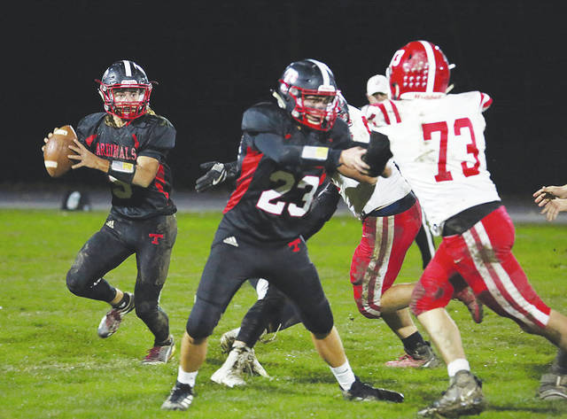 Triad quarterback Coleman Hauck (left) looks to pass during Friday night's regular season game with visiting Cedarville.