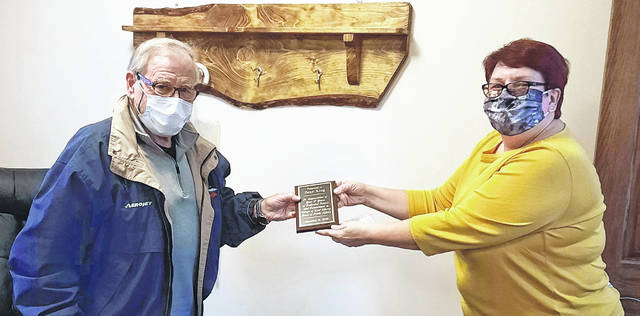 """Dean King, retiring from the West Liberty Board of Public Affairs, receives a plaque of appreciation from board President Jill McKelvey on Monday, December 21. The plaque notes that King is retiring December 31 after """"17 years of dedicated service and commitment."""""""