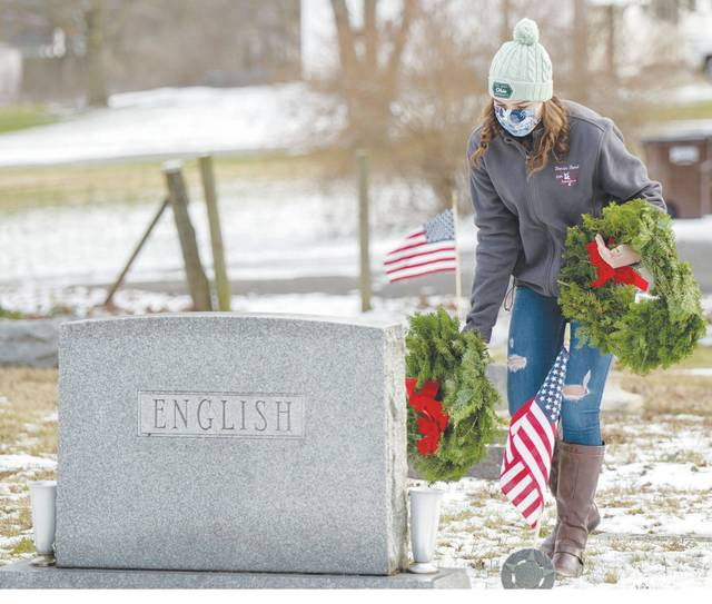 Ava Buell lays a wreath at Evergreen Cemetery in St. Paris on Saturday as part of Wreaths Across America Day.