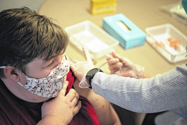 Kim Baldwin, a housekeeper at Messiah Community apartments in Urbana, receives a vaccination to combat COVID-19 earlier this week as part of Phase 1A. Phase 1B of the vaccination process will begin soon.