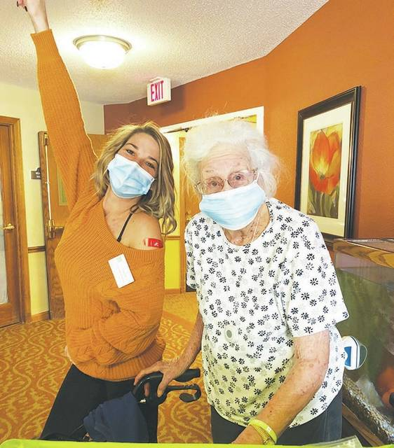 Taylor Phillips, employee of Urbana Place, and Evelyn Noble, resident, celebrate their second dose of the COVID-19 vaccination.