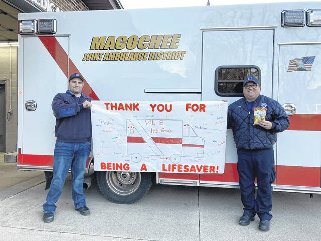 Macochee Paramedics Alan Hager and Kyle Brugler hold a thank-you sign created by West Liberty-Salem first graders. WL-S Elementary students observed The Great Kindness Challenge last week by making signs for local businesses and groups that impact students and the community.