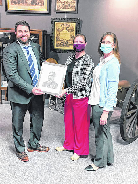 Gregory Harvey, president of the Champaign County Historical Society, accepts a portrait of local educator E.W.B. Curry from Urbana Junior High teachers Sadie Steffan and Amanda Goodwin. While investigating the history of Curry, students found him to be underrepresented at the society's museum on East Lawn Avenue in Urbana, so commissioned his portrait to be done by junior high art teacher Mandy Parker.