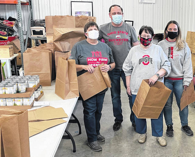"""Chris Harmison, James Landenburg, Julie Balmer and Beth Deere, members of the OSU Alumni Club of Champaign County, take a break from filling bags with non-perishable food at the WhereHouse Food Pantry, 110 W. Church St., on Tuesday. A ministry of the Urbana United Methodist Church, the WhereHouse distributes food and other items the third week of each month. Besides food, The WhereHouse collects and distributes personal hygiene items and paper products. OSU Alumni Club members volunteer once a quarter. Anyone wishing to volunteer or donate items can email wherehouse.dir@gmail.com. The WhereHouse is open the week that follows the third Sunday of each month: 9 a.m.-noon weekdays and 6-7:30 p.m. Tuesday. People stopping by for goods are asked to have a photo ID, proof of Champaign County residency and (if possible) bags or boxes for their items. For more info, visit urbanaumc.com and scroll down to """"the WhereHouse."""""""
