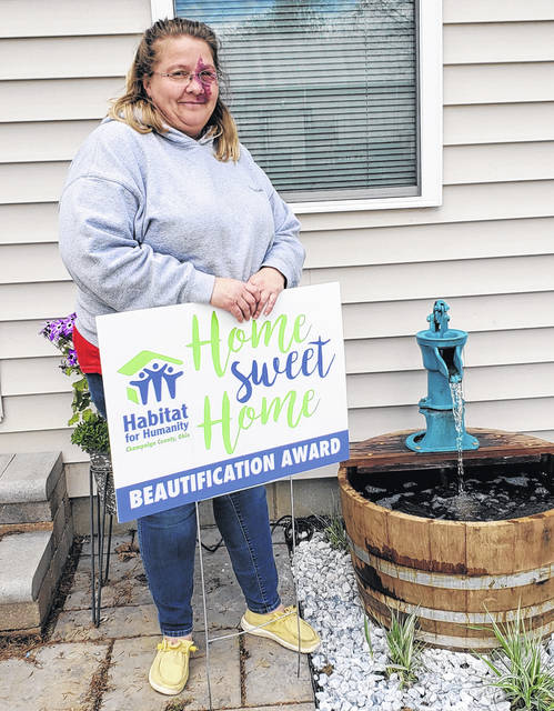 Melanie Blankenship stands with her award at her St. Paris home constructed through Habitat for Humanity Champaign County Ohio.