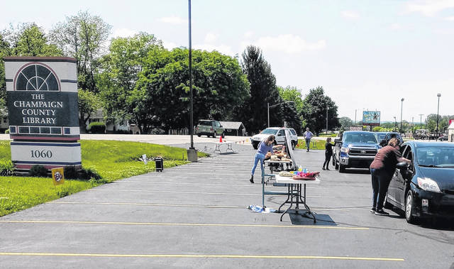 Cars line up for summer reading program registration on June 4 at the Champaign County Library on Scioto Street.