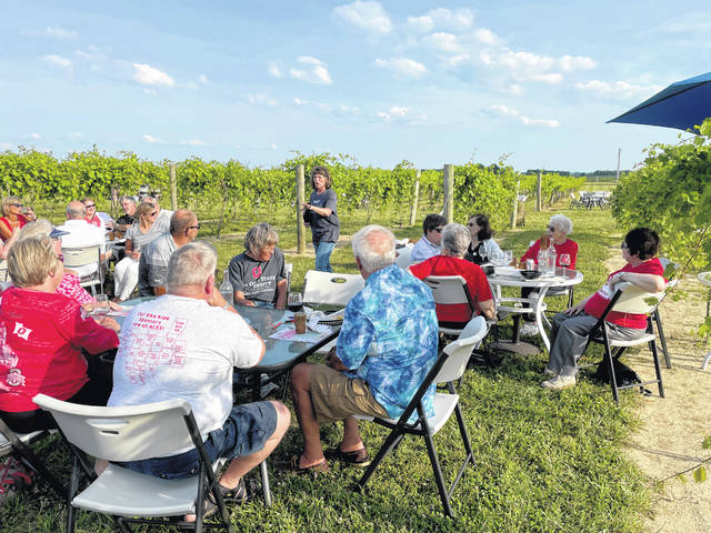 While attending a Meet and Greet on June 26, the members of the Ohio State Alumni Club of Champaign County enjoy the fresh air among the vines as they listen to part-owner Connie Eichenauer tell them about the beginnings and operation of the Dragonfly Vineyard. The Buckeyes enjoyed food and fellowship and are looking forward to more chances to get together. The next social event is the Summer Send-Off on July 25 at the Pretty Prairie Farm. This year all current OSU students, not just freshmen, are being invited to join the alumni.