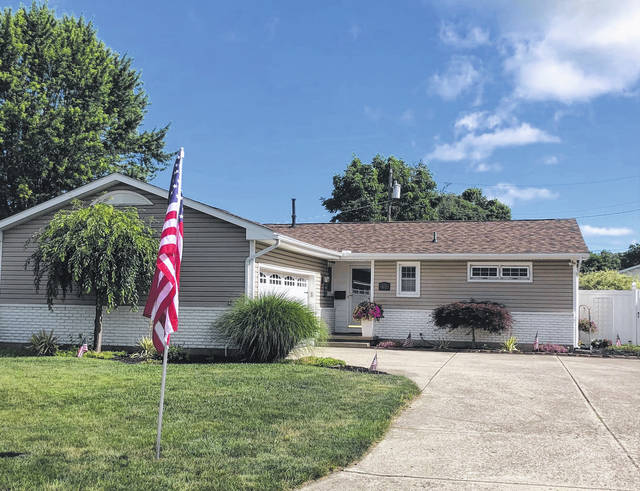 A flag is shown at a residence on Carriage Lane.
