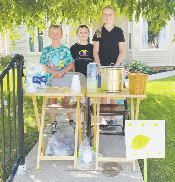 Three Urbana children opened a lemonade stand at 303 E. Court St. to help refresh passersby like the postal carrier. Pictured are Lyle Rice, Brant Markin and Lola Rice, who treated the postal carrier to a free glass of lemonade. The postal carrier, Andre Vactor, took their photo to recognize them for their kindness.