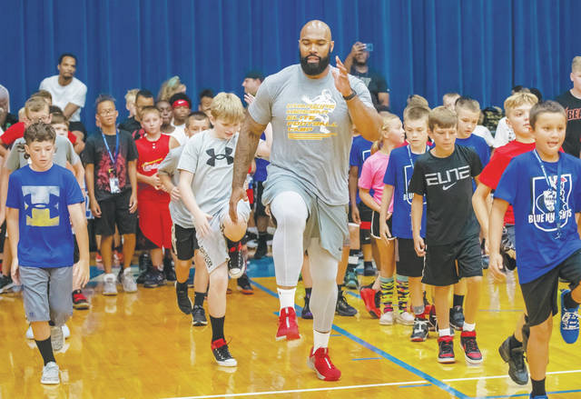 Former Ohio State and NFL player Doug Worthington shows campers how to do a drill during the Charg1ng Heisman Elite Football camp on the campus of the former Urbana University on Friday.