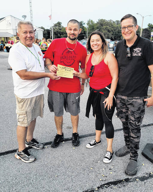 """Shown is the winner of the """"wings contest"""" held during the Balloon Festival at Grimes Field on Saturday. Pictured left to right: Elton Cultice, event chairman, John Evans, winner, Amber Weaver, owner of The Wing Bar and Mark Mefford, general manager of the Wing Bar in Urbana. The contest was sponsored by The Wing Bar and Mr. Evans won a $75 gift certificate to the restaurant by consuming 20 wings in five minutes! Some were mild, some were spicy and some were hot – he ate them all! Congratulations to Mr. Evans and a big thank you to The Wing Bar for sponsoring the contest!"""