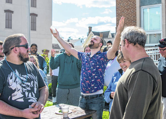 Alex Wood throws his arms in the air in victory after being announced as the hot pepper eating contest winner. The pepper eating contest was part of the Chili Cook-off and Festival in downtown Urbana on Saturday.