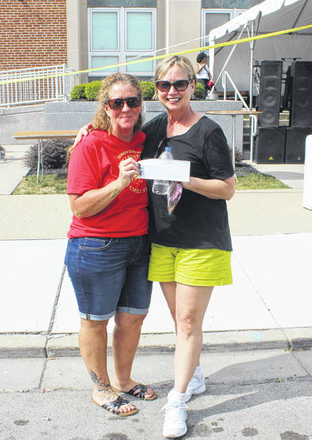 Pictured is the 2019 first place salsa winner, Deborah Grogan (right), receiving the $100 prize from festival committee member Alyssa Hunt Dunham.