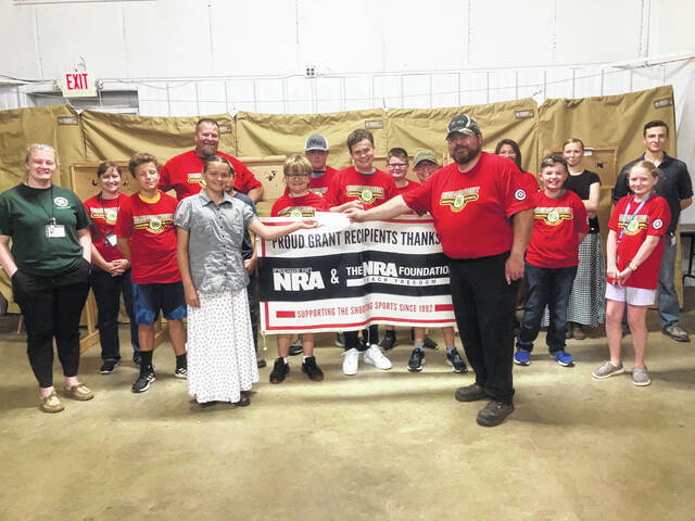 FNRA committee member Ashley Howell is shown presenting a check to the shooting club treasurer, flanked by members and advisors of the 4-H club.