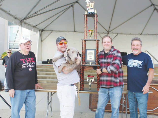 Urbana Mayor Bill Bean (left), the cook-off committee chairman, presents the trophy and $1,000 prize monies to first place Chili Cook-off winning team, the Funky Bovine Chili Co.