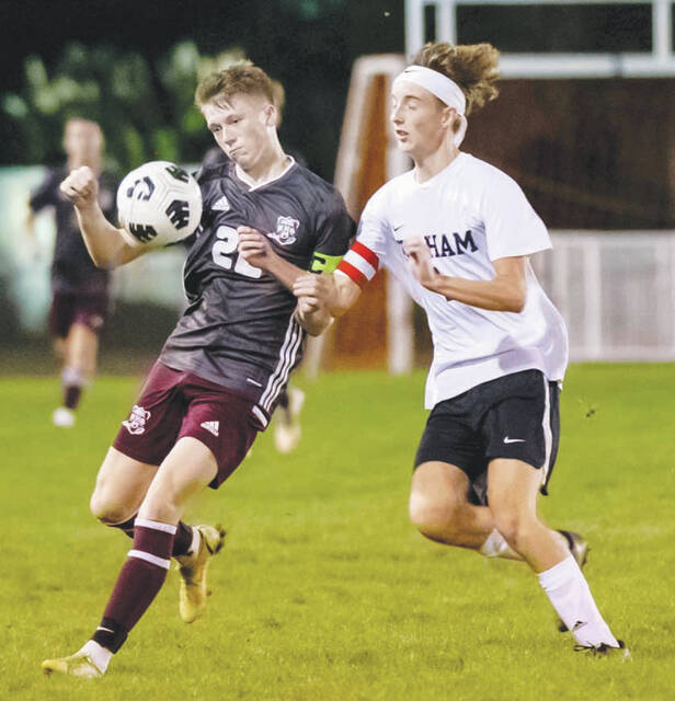 Urbana's Oliver Grim (left) vies for the ball with Graham's Ethan Daubenspeck during a game at UHS.
