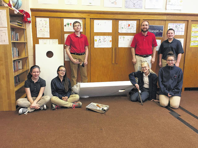 Erin Miller | Galion Inquirer Students in Mr. Shull's seventh- and eighth-grade class at St. Joseph's Catholic School in Galion are pictured with the cornhole boards they built for auction at the upcoming Spring Fundraiser on March 17 at 6:30 p.m.. From the left are Leah Sheets, Wensday Tomecko, Andrew Adkins, Alie Hall, Lilly Gosser, Nathan Barre, and Mr. Shull.