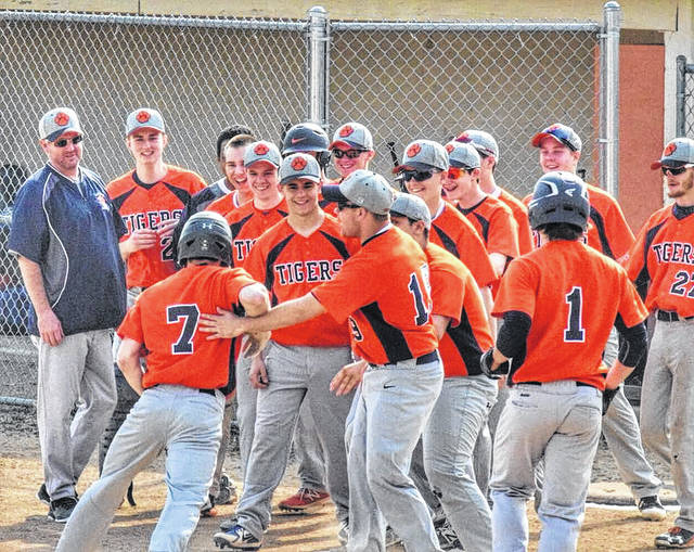 Photo courtesy of Angie Gibson Utz Galion's Mitch Dyer (7) approaches home plate and a mob of teammates after belting a two-run home run on Friday as the visiting Tigers shutout the hosting Mansfield Senior Tygers; 8-0.