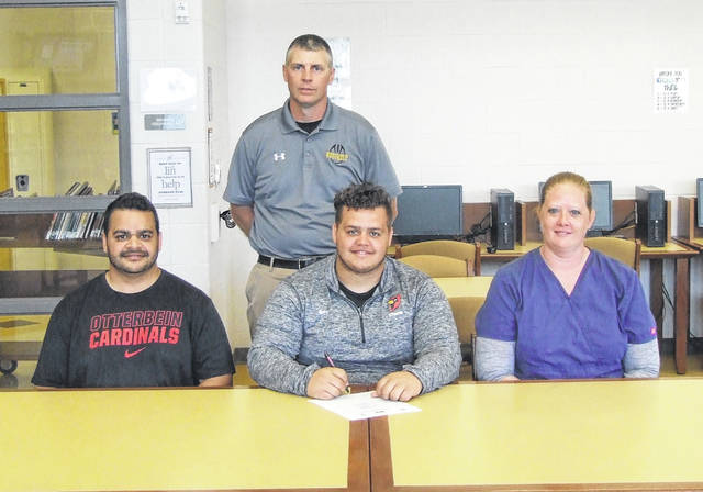 Northmor's Tyson Moore (center) signs his letter of intent to play football for Otterbein. Sitting with him are his parents, Bernie (l) and Sue. Standing is Knight head football coach Scott Armrose.