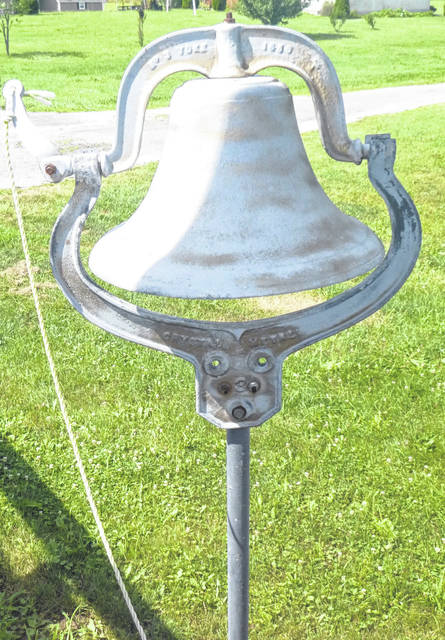 A large cast iron dinner bell sits outside.