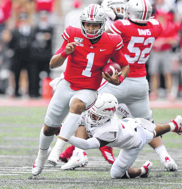 Photo by Don Speck Ohio State #1 Quaterback Justin Fields runs out of the tackle of Florida Atlantic #9 safety Quran Hafiz and heads for the endzone for a touchdown at Ohio Stadium on the campus of The Ohio State University on Saturday.