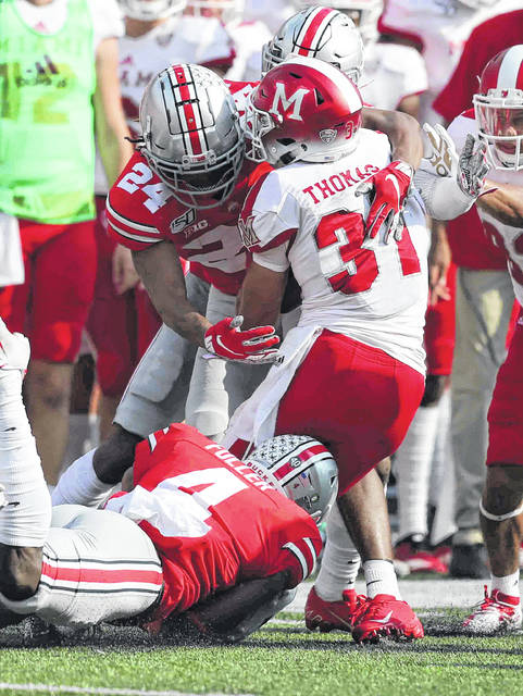 Ohio State's Jordan Fuller(4) and Shaun Wade tackle Miami of Ohio's Maurice Thomas during Saturday's game against Miami of Ohio at Ohio Stadium in Columbus.