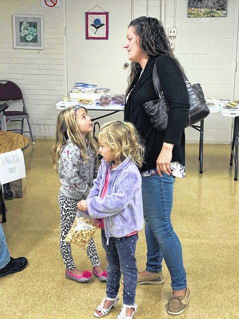 Photo by Jodi Myers Willow and Grace Kiser, and their mom Jenna Kiser, ponder additional purchases at last week's sale at last week's Golden Age Center sale and fundraiser. They had already bought some pop corn.