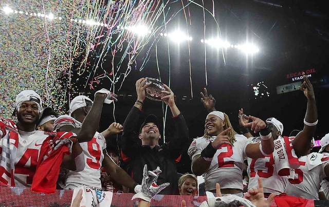 Ohio State head coach Ryan Day celebrate with his team the Buckeyes third straight Big 10 title after beating Wisconsin in the Big Ten Championship game at Lucas Oil Field Saturday.