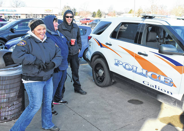 Photo by Don Tudor. Galion police Dispatcher Angie Scott, left, FOP member Lynn Sterling and Officer Tim Johnson were stationed outside Discount Drug Mart in Galion on Saturday during Fill the Cruiser day. They accepting donations of gifts, food and money for the less fortunate this holiday season. Also present, but not in the picture, was Officer Steve Knapp.